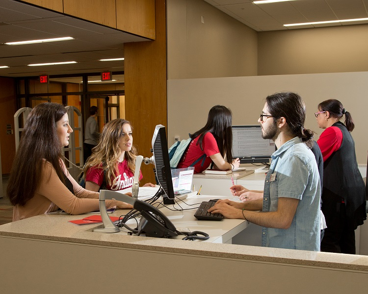 Librarians assisting students at the Scholars' Commons reference desk
