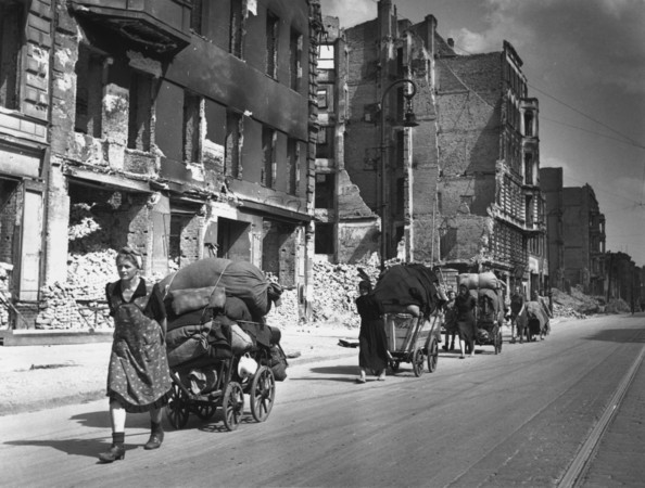 Female Berliners pulling large carts loaded with sacks and possessions through the bomb-damaged streets of Berlin.