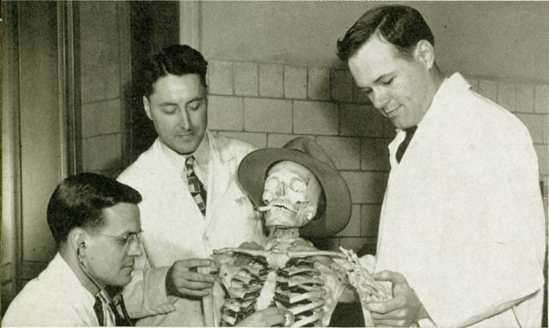 Three doctors study an articulated skeleton with a cigarette in its mouth and a cowboy hat on its head