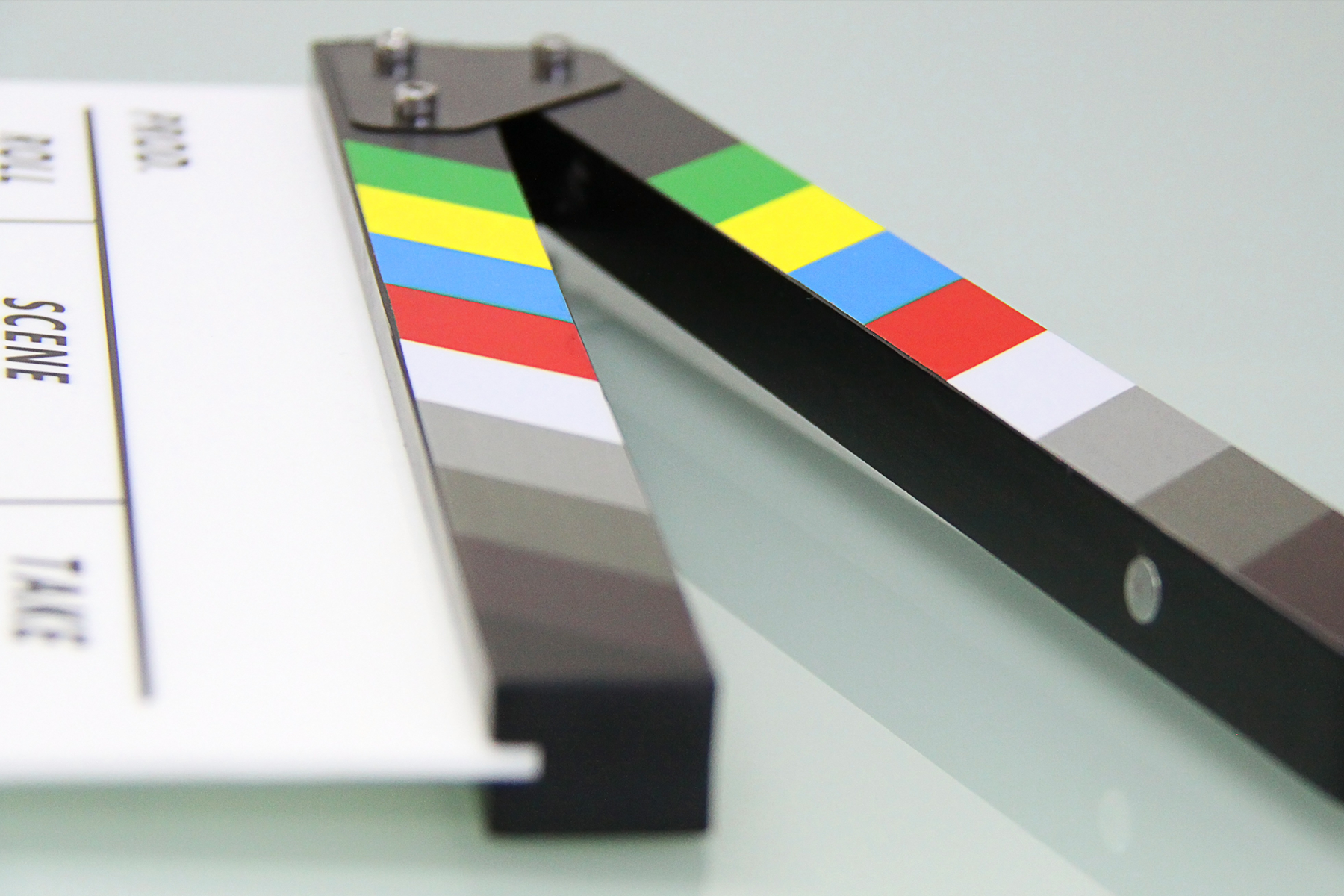 a clapperboard rests before a white background