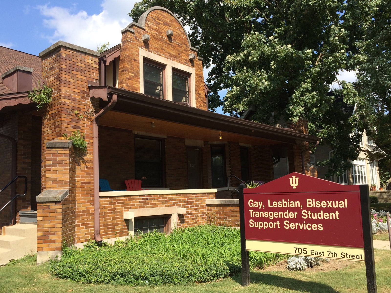 "A sign in front of a brick house with a front porch says ""Gay, Lesbian, Bisexual, Transgender Student Support Services 705 East 7th Street"""