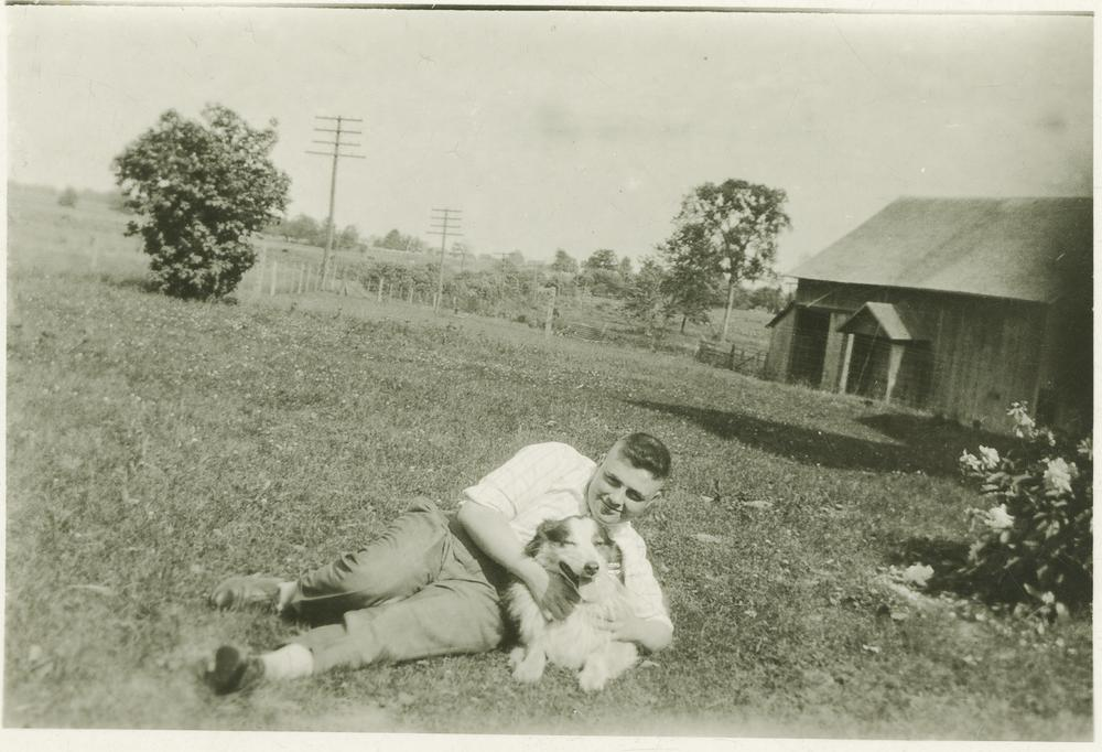 Wells lying in grass next to collie(?) dog, with house and fields in background