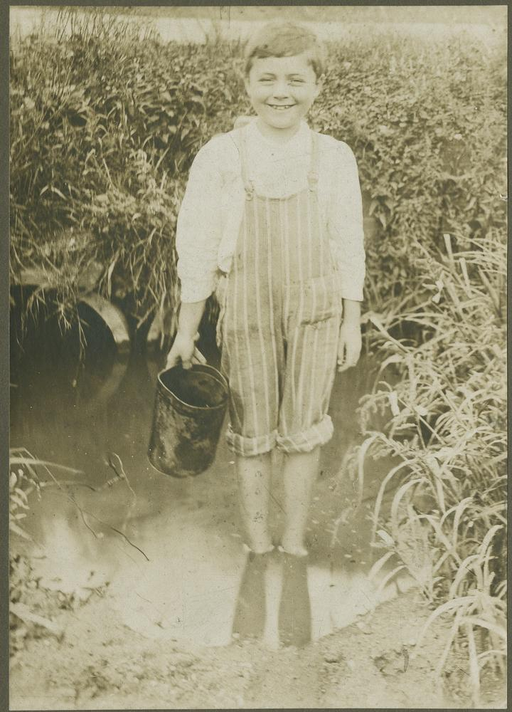 Young Wells standing in creek and holding bucket