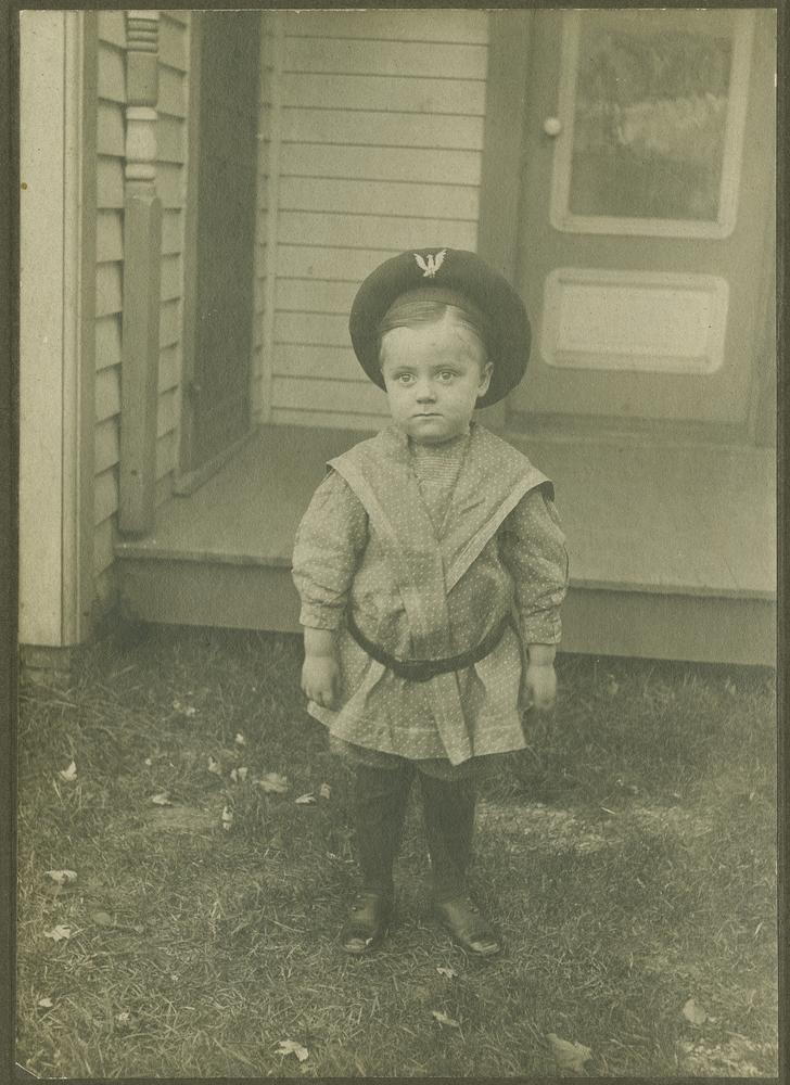 Toddler Wells wearing hat and standing in front of a doorway outside a house
