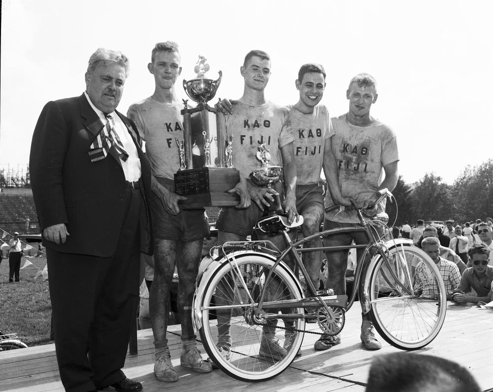 Wells posing with winning cyclists of the 1956 Little 500 race and their trophies