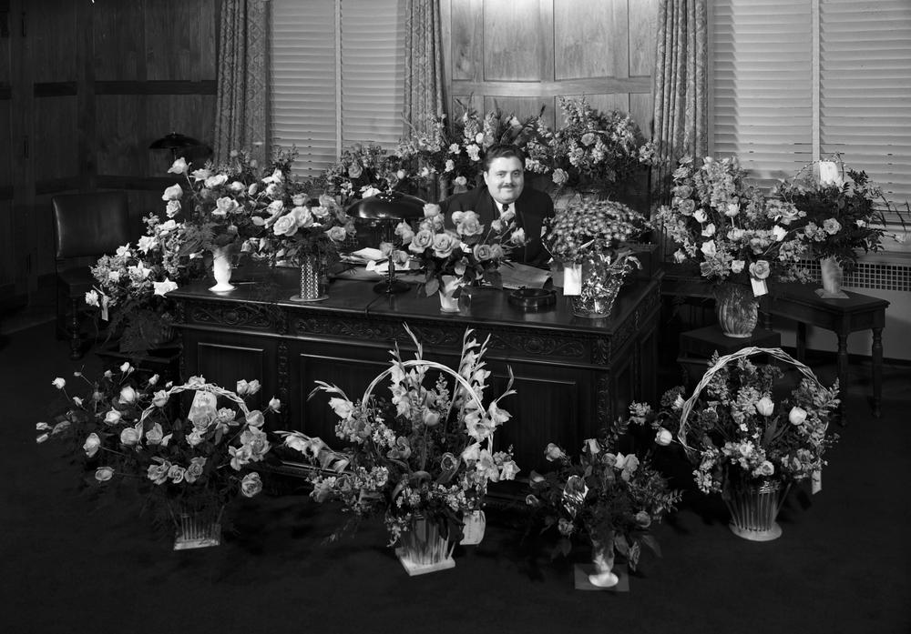 Herman Wells sitting at desk surrounded by flower arrangements.