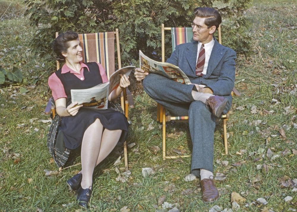 Clarence and Mary Flaten reading newspapers in lawn chairs (colorized photograph)