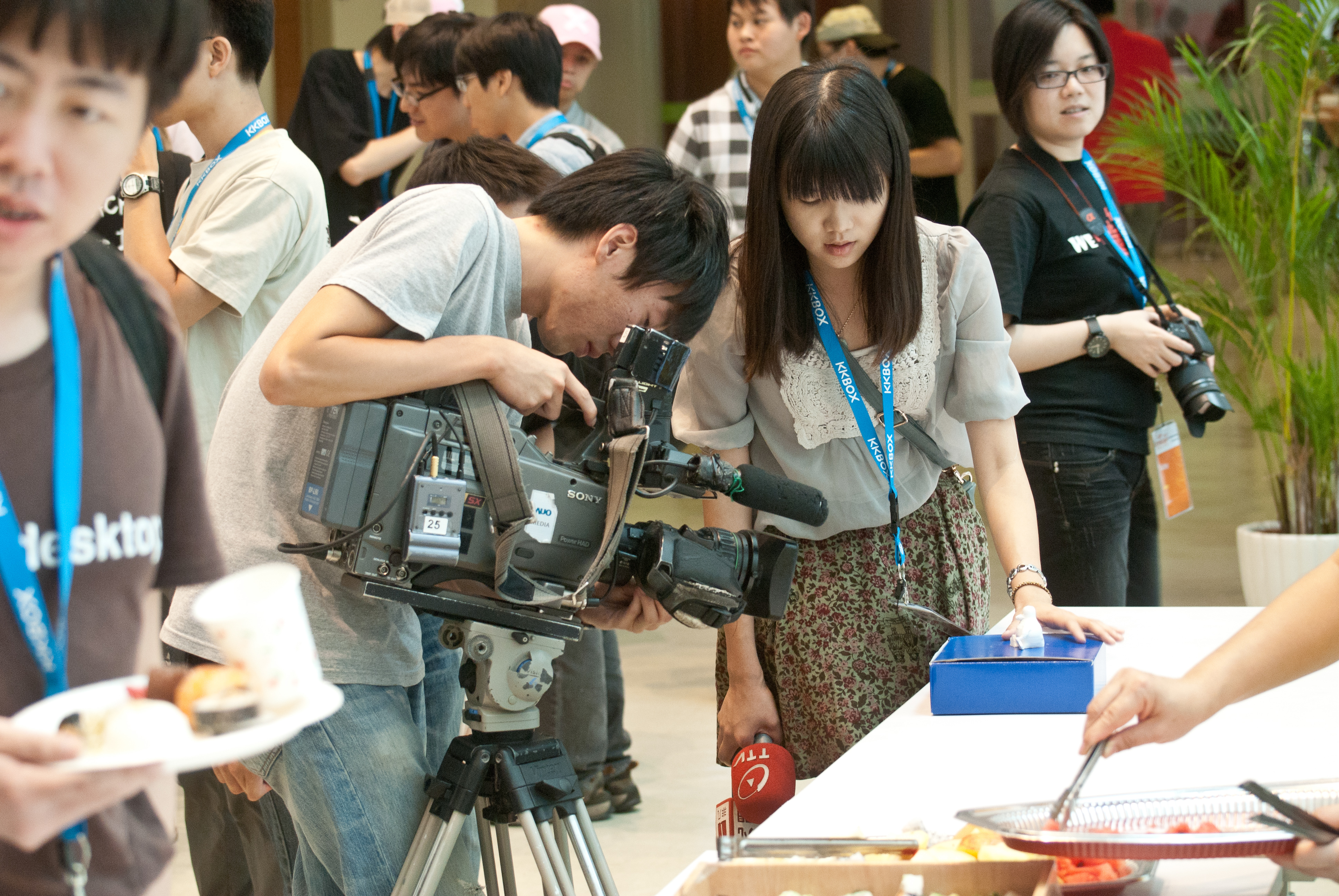 A cameraman looks down into a camera which is pointing at a small statue on a blue box. A reporter looks at the statue as if talking about it.