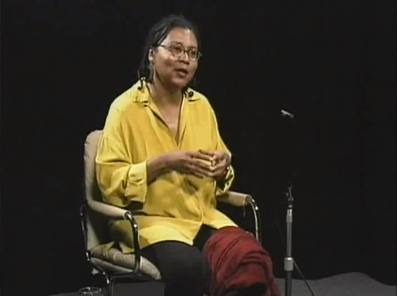 bell hooks sitting in a chair taken from the documentary Cultural Criticism and Transformation.