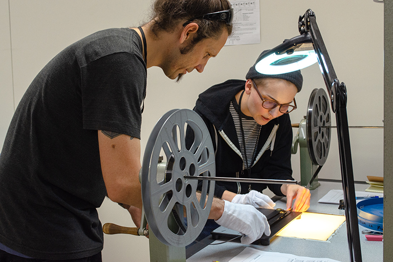 A man and a women work together at a table. Film and film reels are in the foreground.