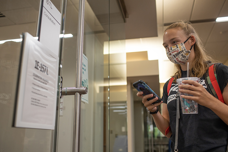 A student looks at her phone to confirm a sign showing a room number