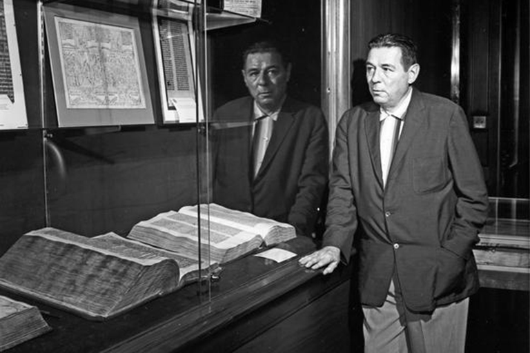 A black and white photo of a man in a coat and tie standing in front of a display case full of books in the 1960 Lilly Library.