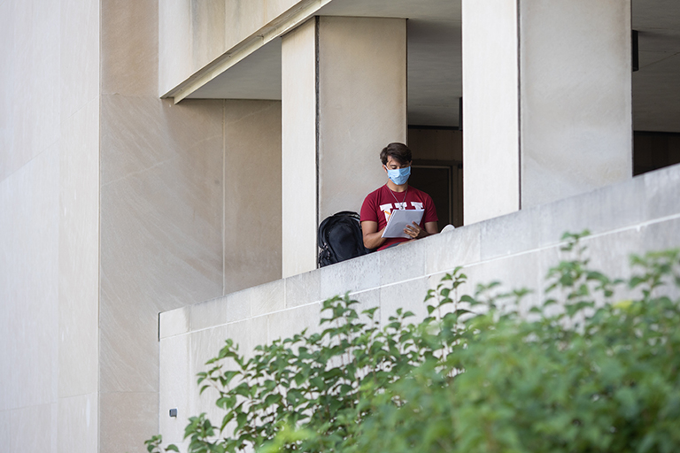 A student wearing a red IU tshirt and a mask studies outside the Wells Library