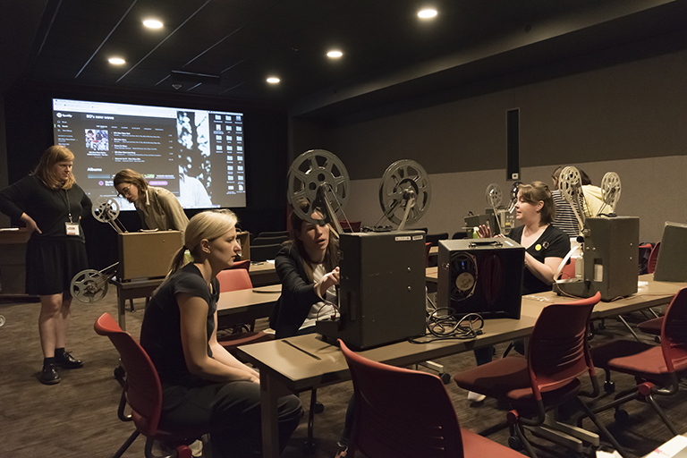 several students are in a darkened film screening room working with projectors.