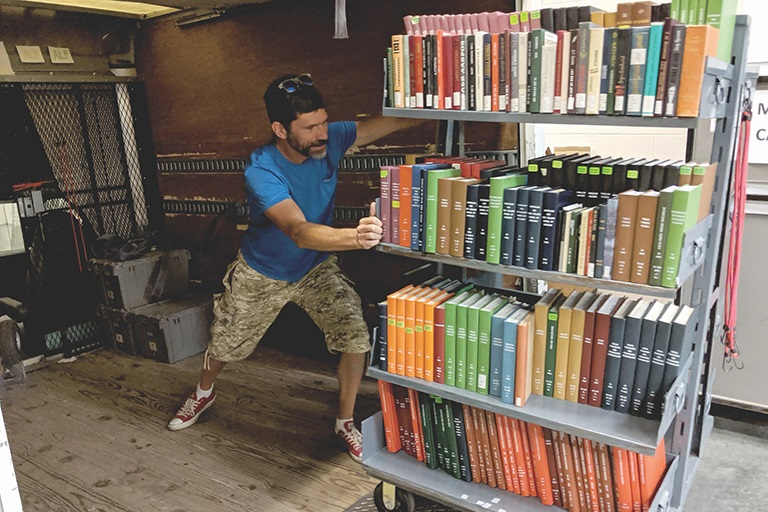 Staff member pushes a tall, heavy cart four shelves high, filled with library books.