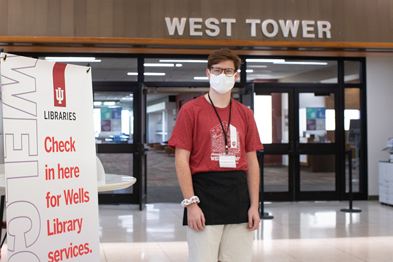 A student wearing a uniform stands in the Herman B Wells Library lobby.