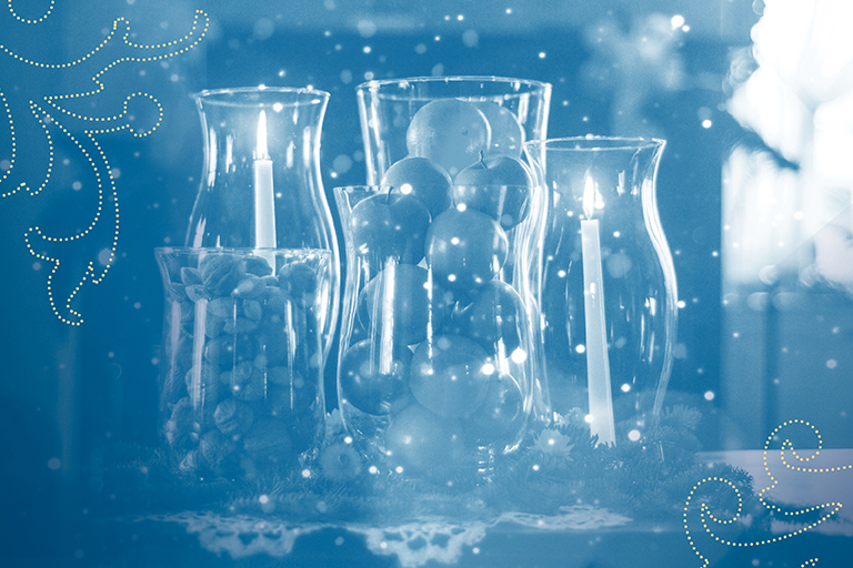 blue and white image of group of five glass hurricanes with candles and decorative fruit and nuts