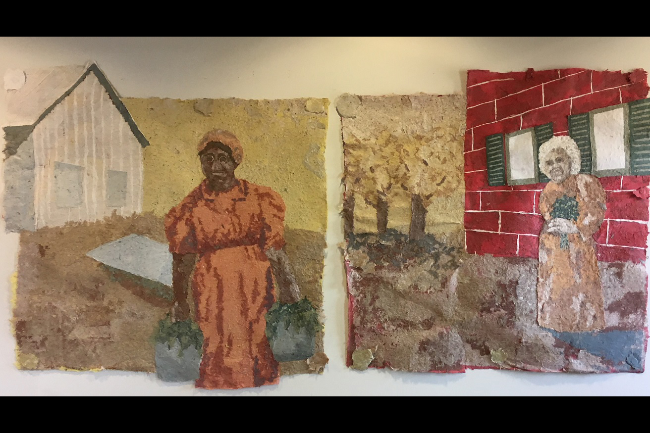 A photo of two paper pulp murals featuring women working in the Wylie House gardens.