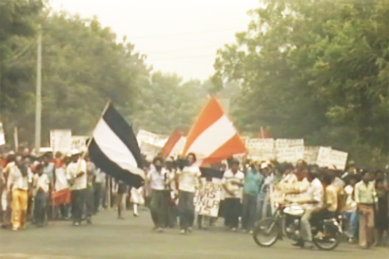 A color photo from 1987 shows protestors with flags in Nicaragua