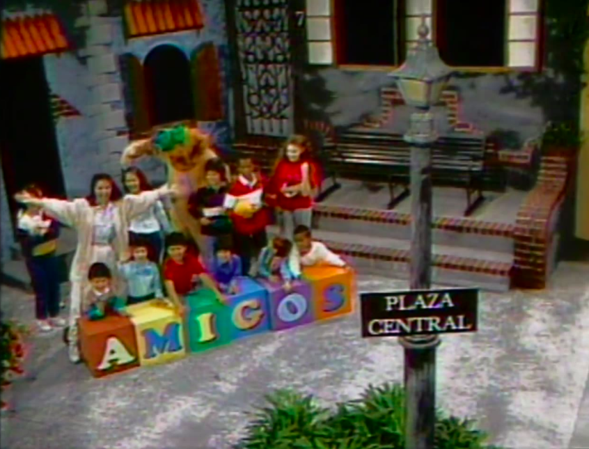 title card for Amigos showing kids and the show's hosts gathered around blocks on a street corner stage