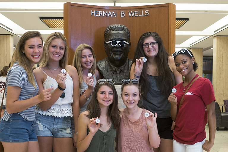Herman B House Party attendees with bust of Herman B Wells in Wells Library 2015