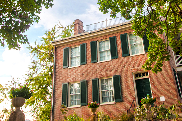 A brick two story house with black shutters and a widow's walk, built in 1840.