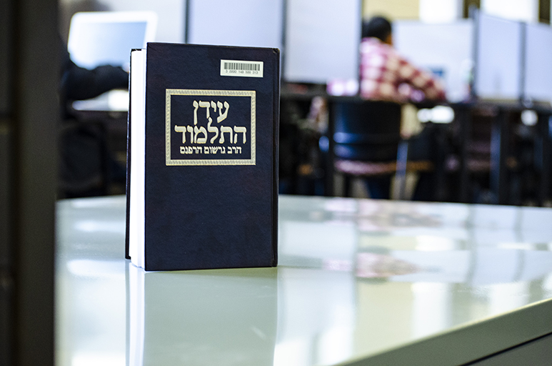 Image of a Hebrew book on a table at Wells Library