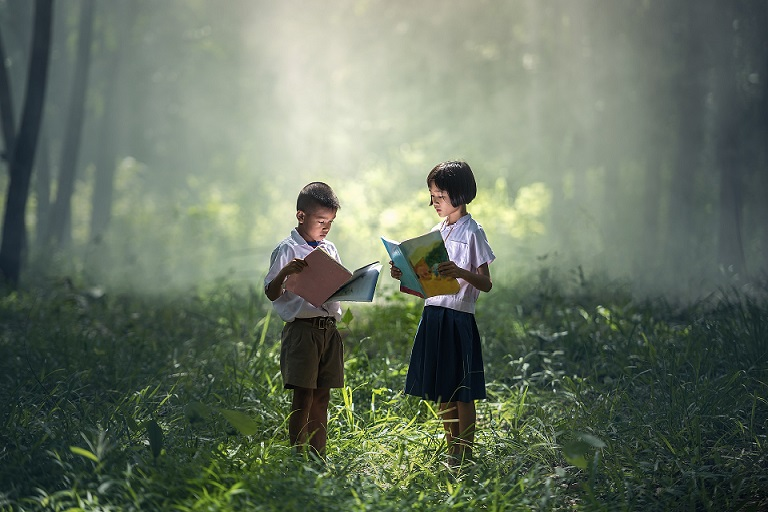 Children reading books in a forest