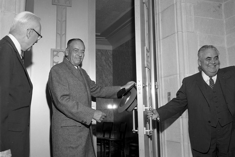 A black and white photo of one man opening a large door for another man in a coat holding a hat.