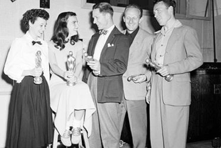 Black and white photo of students in about 1950. Group is standing in a semicircle with an aware