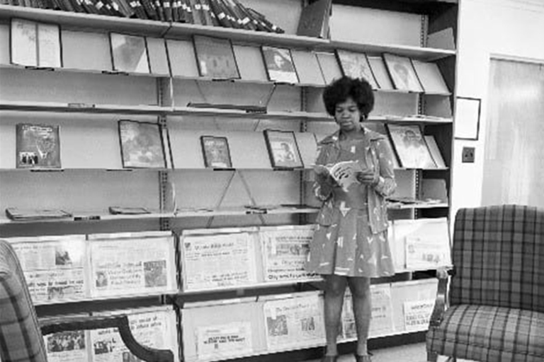 In a black and white photo, a black women reads a book in front of a periodical book shelf display.