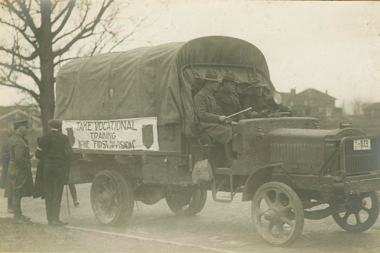 "WWI era vehicle with banner on the side reading ""Take Vocational Training in the 'First Division'"""