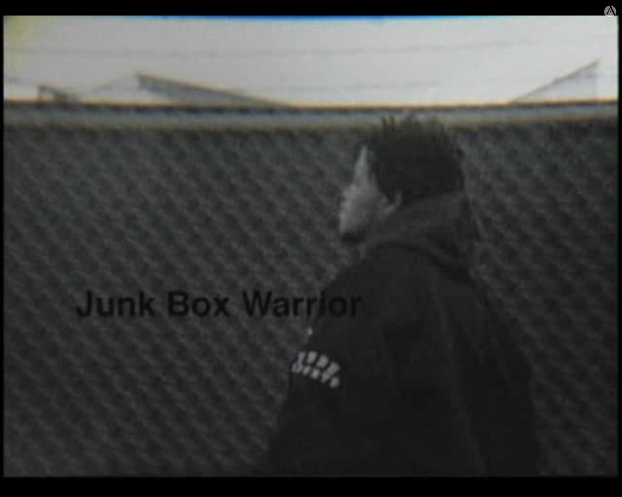 Black and white image of Marcus Rene Van, narrator of Junk Box Warrior, standing in front of a fence. The words Junk Box Warrior are written left and below center of the image.