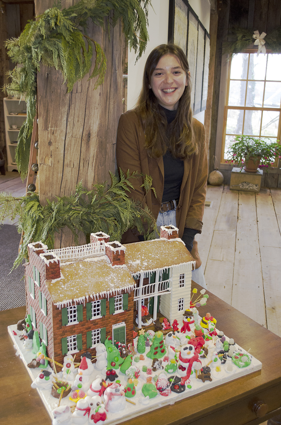 Image of student artist with a gingerbread model of the Wylie House