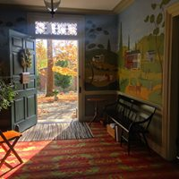 Image of interior front hall of Wylie House Museum, view from inside looking out of open front door.