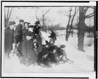 Children on sleds at the top of a hill in wintertime