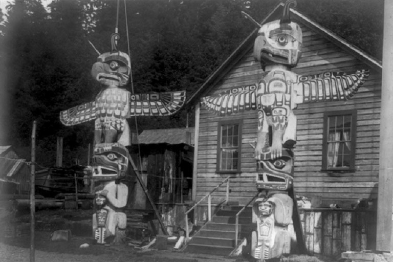 Two totem poles in front of a wood frame house in the Nimkish village, Yillis, on Cormorant Island.