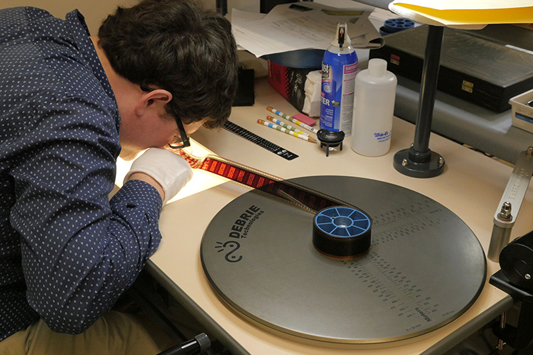 Man leans over large film reel mounted to a table.