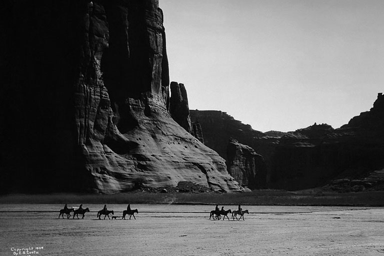 Seven Navajo horseback riders cross from left to right through a picturesque canyon.