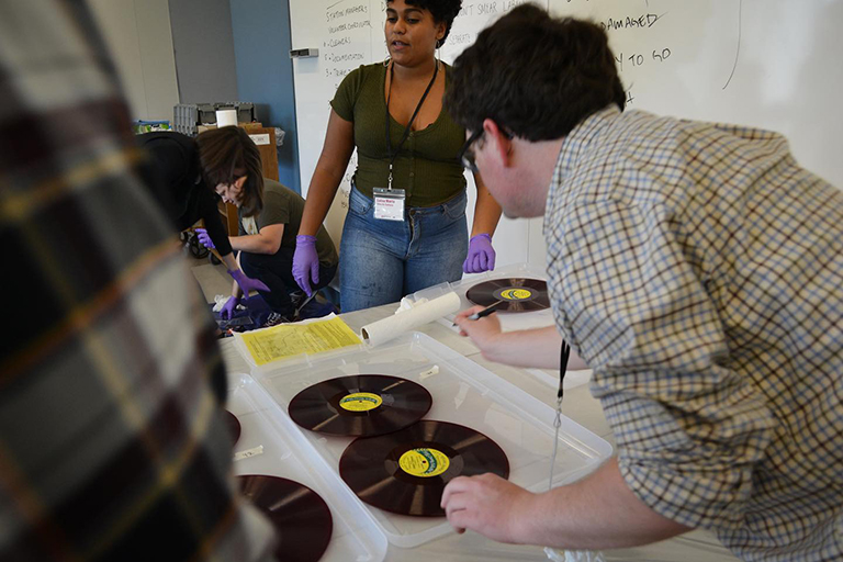 A group of students examines records on a word table.