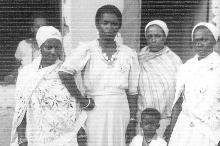 Four women and a little boy face the camera while standing in front of a building.