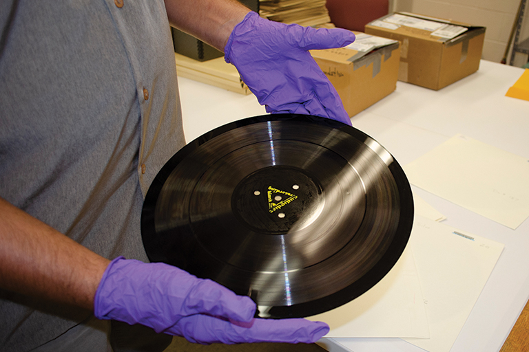 A man wears purple gloves to hold a 1940's original field recording disc