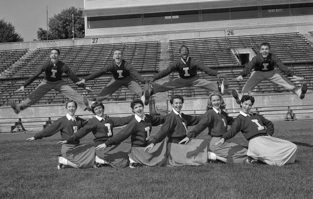 A black and white photos shows college cheerleaders in the 1950s. Four males are jumping and yelling above six females posed in a row.