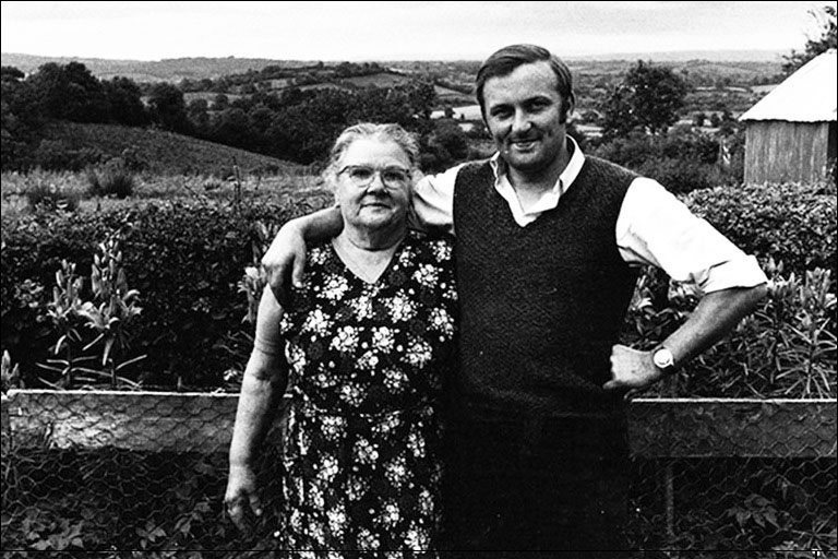 A young man stands with his arm around an older woman in rolling countryside.