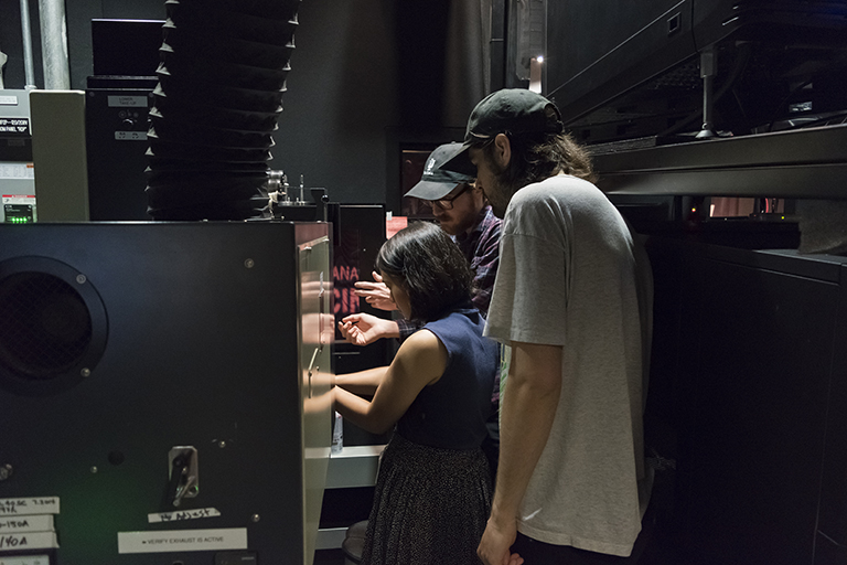 Three people are in a projection booth for a cinema