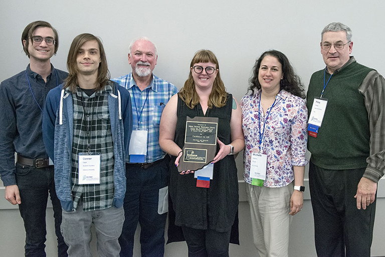 Image shows a row of men and women holding an award in the center.