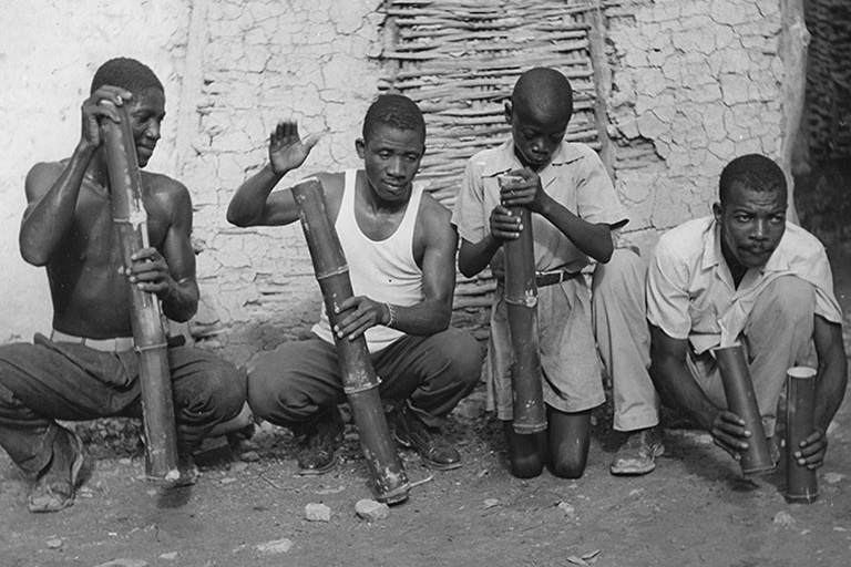 Four Haitians squat on the ground, making music with bamboo stamper.