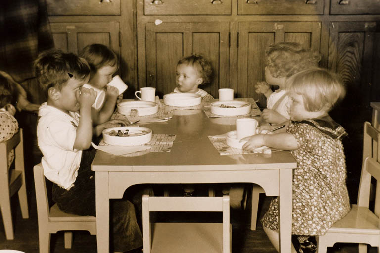 Great Depression era children sitting around a wooden table sharing a meal