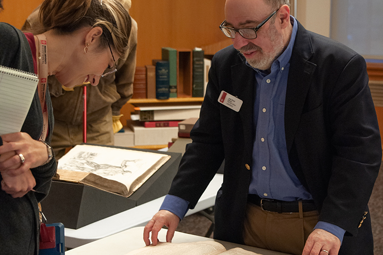 A male librarian discusses a large book with a female library visitor