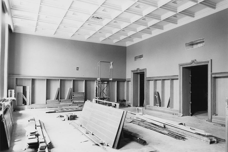 Lilly Building construction in 1959. Empty room with construction materials piled high. Faded black and white image.
